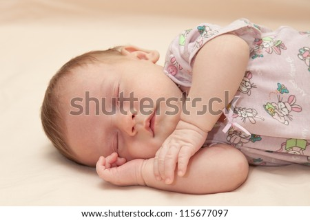 Newborn baby sleeping on blanket with his hand under his cheek. Selective focus on baby face - stock photo
