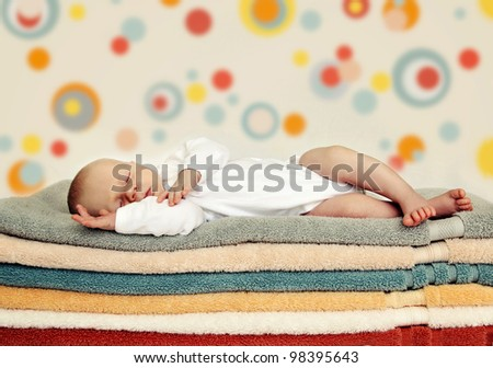 Newborn baby sleeping on colorful towels. Soft focus, very shallow DOF. - stock photo
