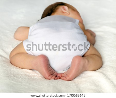 newborn baby sleeping on white. rear view. butt in a diaper, with a adorable crossed legs and feet - stock photo