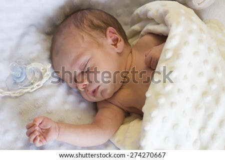Newborn baby sleeping with a pacifier on a white blanket. - stock photo