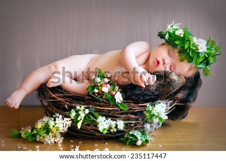 newborn baby sleeps in a nest with a wreath on head - stock photo