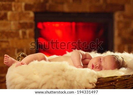 newborn baby sleeps in basket near the fireplace - stock photo