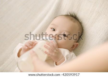 newborn baby sucking bottle - stock photo