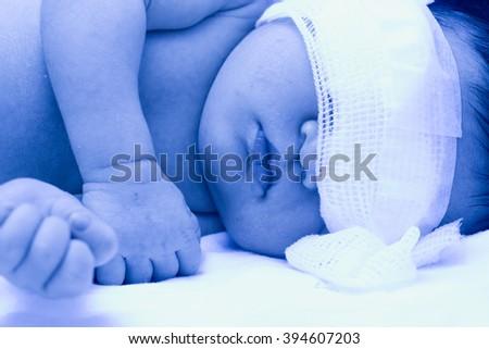 Newborn baby under ultraviolet lamp in the incubator. - stock photo