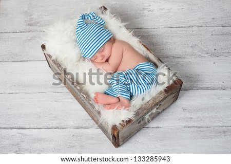 Newborn baby wearing blue and white striped pajamas and sleeping in a vintage, wooden, soda pop crate. - stock photo