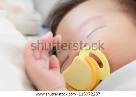 Newborn beautiful baby sleeping with pacifier. Closeup portrait - stock photo