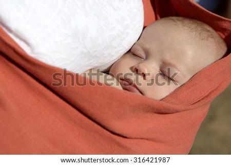 Newborn boy sleeping in the orange baby sling carrier outdoor - stock photo