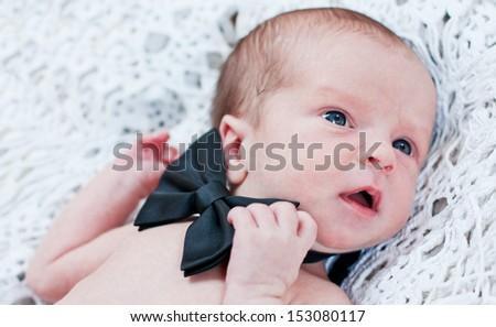 newborn boy with butterfly cute gentleman on white bedspread - stock photo