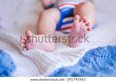 Newborn feet. Sweet baby heel in a gentle natural  morning light. - stock photo