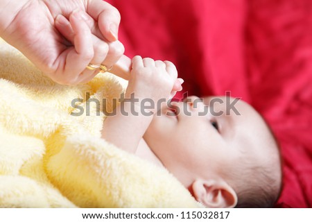 Newborn - first touches with mother hand - stock photo