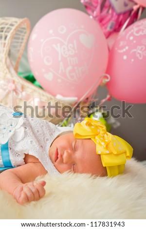 Newborn girl sleeping by pink balloons - stock photo