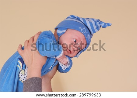 Newborn in nursery mother held up her hands - stock photo