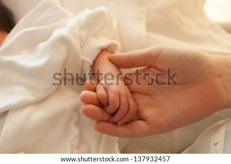 Newborn infant toddler baby hands a few days old holding mothers hand - stock photo