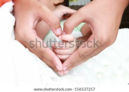 Newborn infant toddler baby hands a few days old holding mothers hand.  - stock photo