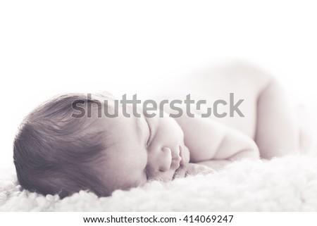 Newborn sleeping alone in white  - stock photo