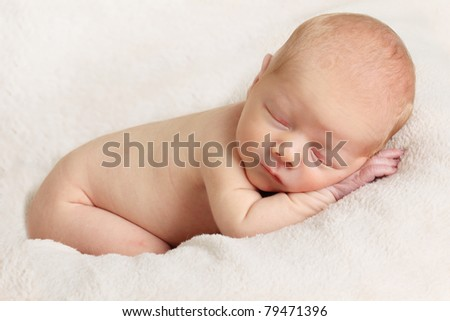 Newborn sleeping baby boy on a white blanket. - stock photo