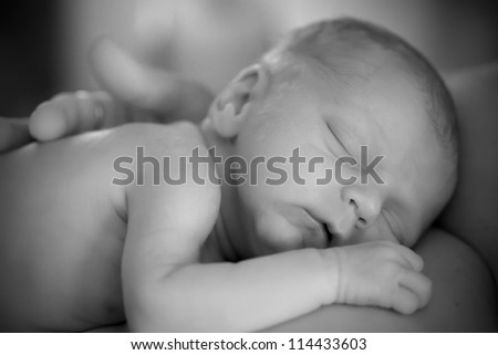 Newborn sleeping infant on mother black and white - stock photo