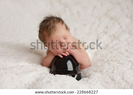 Newborn sleeping with arms on a baseball helmet - stock photo