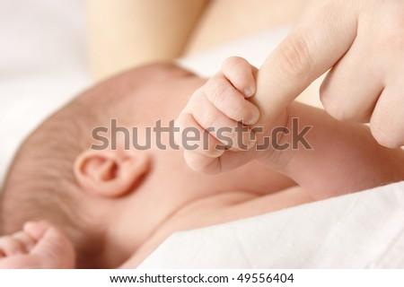 Newborn sucks mother's breast and grips her finger, breastfeeding, shallow DOF - stock photo