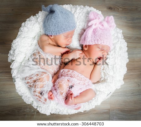newborn twins - a boy and a girl sleeping in a basket - stock photo