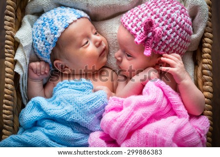 Newborn twins lying down inside the wicker basket - stock photo