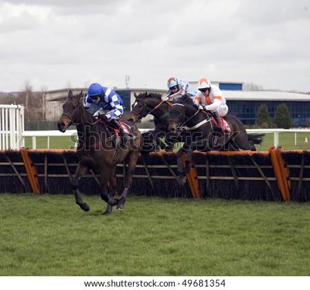 NEWBURY, BERKS- MAR 27: Jockey Aidan Coleman (blue and white) takes lively fling over hurdles in the first race at Newbury Racecourse, UK, March 27, 2010 in Newbury, Berks - stock photo