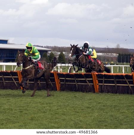 NEWBURY, BERKS- MAR 27: Jockey Alex Merriam takes evella over hurdles in the 3rd race at Newbury Racecourse, UK, March 27, 2010 in Newbury, Berks - stock photo