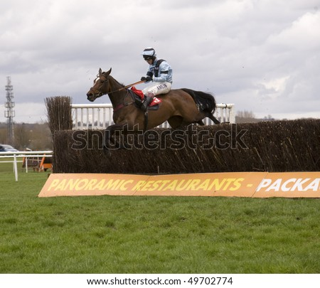 NEWBURY, BERKS - MAR 27: Jockey Richard Johnson takes Calusa Crystal  over fences in the second race at Newbury Racecourse, UK, March 27, 2010 in Newbury, Berks - stock photo