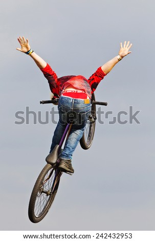 NEWBURY, UK - SEPTEMBER 21: A rider from a freestyle BMX team displays his stunting prowess to the watching public as part of the entertainment show at the Berks show on September 21, 2014 in Newbury - stock photo