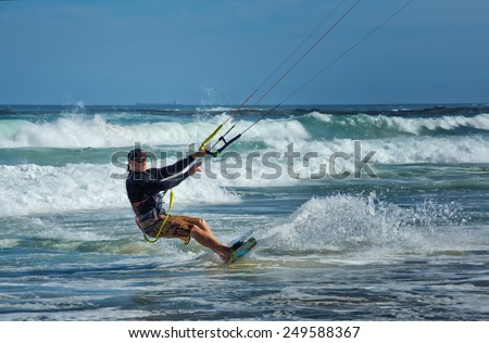 NEWCASTLE,AUSTRALIA - JANUARY 24,2015: A kite surfer enjoys the waves off Nobby's Beach. Newcastle is the 2nd city of New South Wales, after Sydney. - stock photo