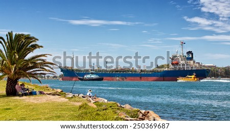 NEWCASTLE,AUSTRALIA - JANUARY 24,2015: A tanker is guided out to sea by the harbour pilot and a tug. Newcastle is the world's leading coal export port. - stock photo
