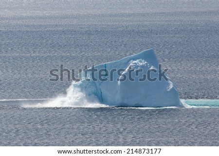 Newfoundland coastal iceberg collapsing and producing waves. - stock photo
