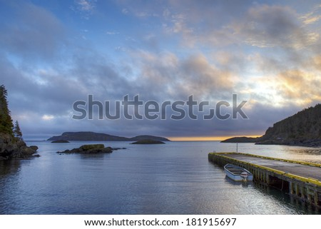 Newfoundland fishing boat at wharf. - stock photo