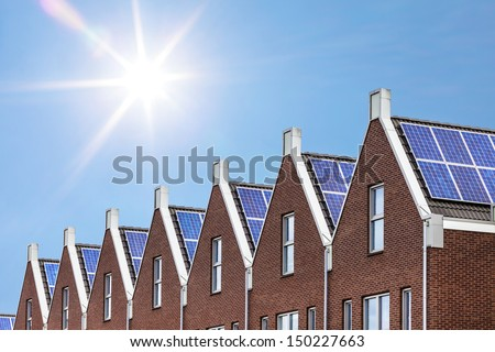 Newly build houses with solar panels attached on the roof against a sunny sky - stock photo