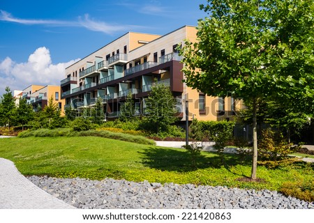 Newly built block of flats with public green area around - stock photo