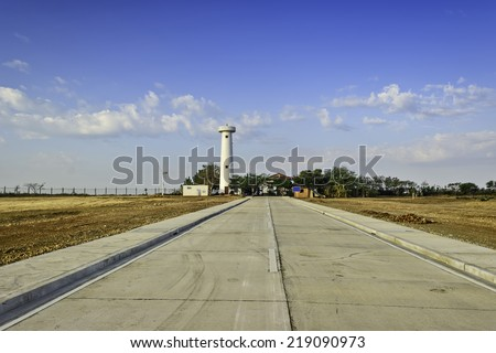 Newly built concrete road leading to a lighthouse undergoing restoration - stock photo