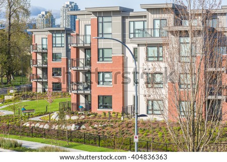 Newly built condos with nicely trimmed and designed front yard in a residential neighborhood in Canada. Street view. - stock photo