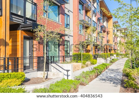 Newly built condos  with nicely trimmed and designed front yard in a residential neighborhood in Canada. - stock photo