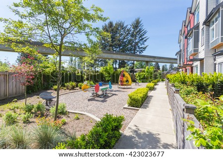 Newly built condos with nicely trimmed and designed front yard in a residential neighborhood in Canada. Kids playground in front of the building. - stock photo