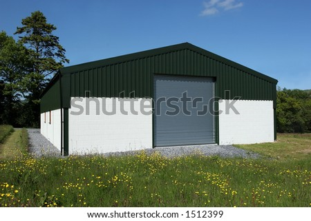 Newly  constructed barn of cream painted concrete block walls with a green metal sheet roof and roller shutter doors, standing in a field of buttercups, with a blue sky and trees to the rear. - stock photo