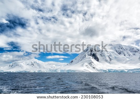 Newly fallen snow covers the mountains in Antarctic peninsula - stock photo