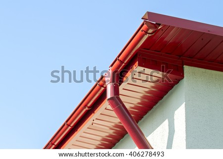 newly installed red rain gutter on house rooftop - stock photo
