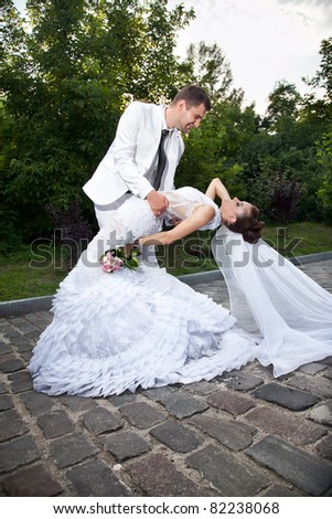 Newly married couple dancing in park - stock photo