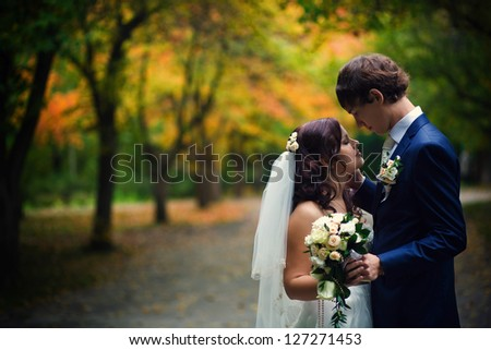 Newly married couple posing in autumn park - stock photo