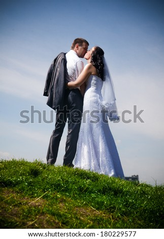 Newly married couple standing on top of hill against blue sky - stock photo