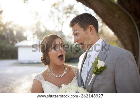 Newly married couple together with surprised look - stock photo