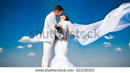 newly married couple.wind lifting long white bridal veil - stock photo