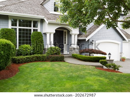 Newly painted exterior of a North American home during summertime with green grass and flower beds  - stock photo