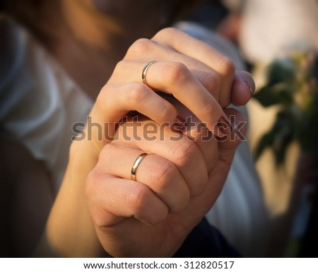 newly wed couple holding each other by their hands - stock photo