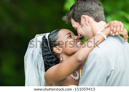Newly wed couple hugging in forest - stock photo